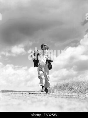 1940S 1950S JUNGE LÄUFT AUF KAMERA AUF LANDSTRAßE HOLDING STRAUß FRÜHLINGSBLUMEN IN EINER HAND - Stockfoto