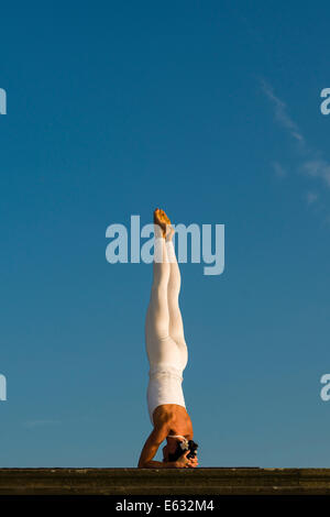 Junge Frau Hatha Yoga im Freien praktizieren, zeigt die Pose Sirshasana, Kopf stand - Stockfoto