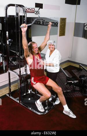 1990ER JAHRE ÄLTERES PAAR MIT HEIMTRAINER - Stockfoto