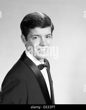 1960ER JAHRE PORTRAIT LÄCHELND TEENAGER TRUG EINEN SMOKING, BLICK IN DIE KAMERA - Stockfoto