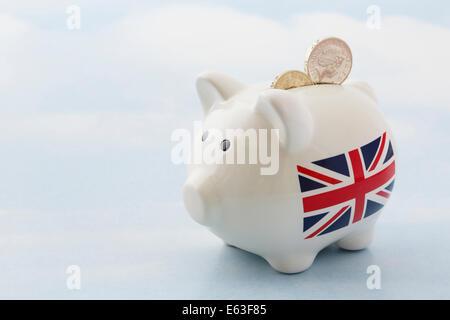 Sparschwein mit britischen Union Jack und zwei Pfund Sterling Pfund-Münzen in Slot auf einem blauen Himmelshintergrund, - Stockfoto