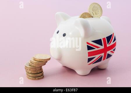 Der britische Union Jack auf Sparschwein auf einem Stapel von Pfund Pound Münzen zur Veranschaulichung von Einsparungen - Stockfoto
