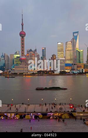 Lastkähne und Skyline von Pudong in der Abenddämmerung, Shanghai, China - Stockfoto