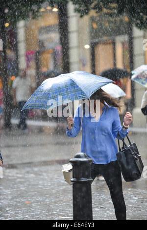 Covent Garden, London, UK. 14. August 2014. Menschen laufen für Cover als ein Platzregen Hits Zentrum von London. - Stockfoto