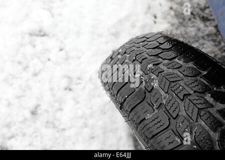 Nahaufnahme von Winterreifen auf einer verschneiten Straße - Stockfoto