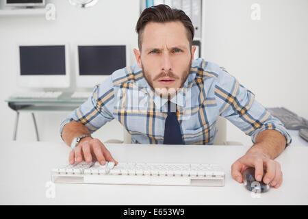 Lässige Geschäftsmann an seinem Schreibtisch arbeiten konzentriert - Stockfoto