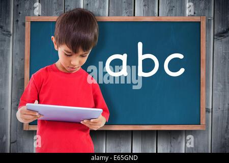 Zusammengesetztes Bild von süsser Boy mit tablet - Stockfoto