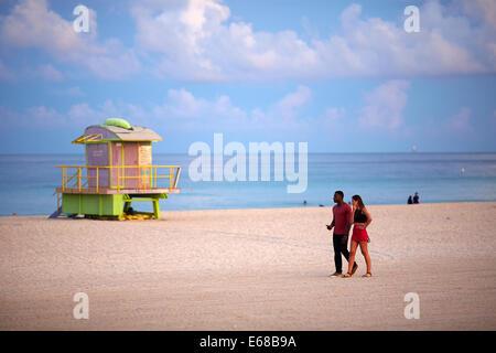 Miami in Florida USA ein Liebespaar Spaziergang am Strand bei Sonnenaufgang ein Rettungsschwimmer Turm - Stockfoto