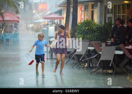 Ein Bild von Mutter und Sohn durchziehen er Straße bei starkem Regen - Stockfoto
