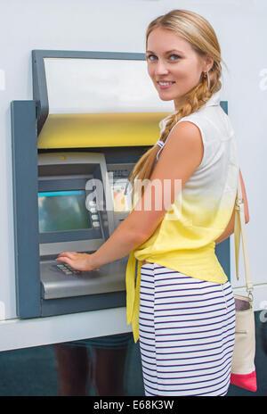 Hübsche Frau an einem Geldautomaten Geld abheben. - Stockfoto
