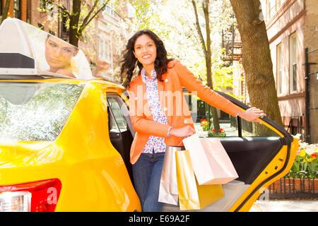 Gemischte Rassen Frau raus aus dem Taxi auf Stadt Straße - Stockfoto