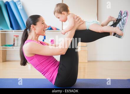 Kaukasische Frau halten Baby auf Yoga-Matte - Stockfoto