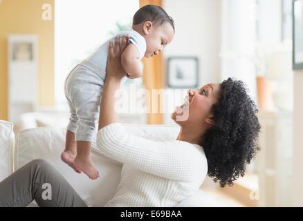 Mischlinge Mutter mit Baby auf Sofa spielen - Stockfoto