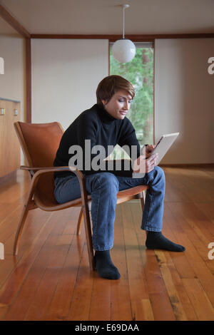Kaukasische Frau mit Tablet-Computer im Sessel - Stockfoto