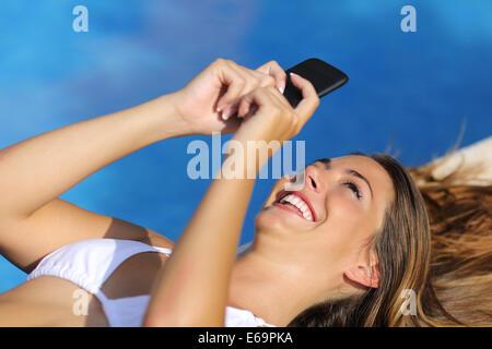 Nahaufnahme einer lustige Frau, die mit ihrem Smartphone im Sommerurlaub mit blauem Wasser im Hintergrund - Stockfoto
