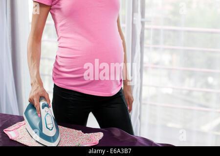 Porträt von unkenntlich schwangere Frau, die ihr zukünftiges Baby Kleidung bügeln - Stockfoto