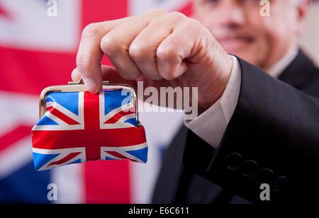 Geschäftsmann hält eine Union Jack Geldbörse zu der Auffassung, vor einem Union Jack Hintergrund steht. - Stockfoto