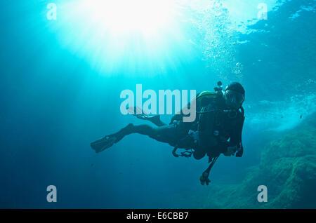 Sonnenstrahlen und Taucher Schwimmen unter Wasser, Europa - Stockfoto
