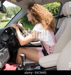 Falsche Körperhaltung und schlechte Fahrposition. Junge weibliche Autofahrer beugte sich über das Lenkrad eines - Stockfoto