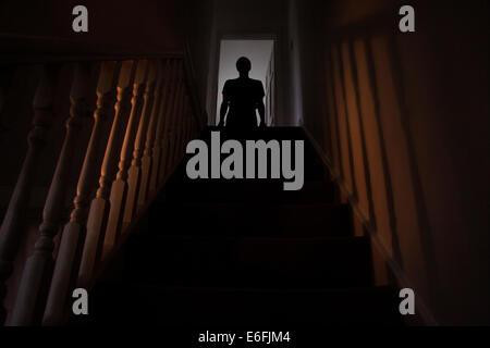 Silhouette eines Mannes stehen an der Spitze einer Treppe, Schatten an den Wänden des Lichts unter. - Stockfoto