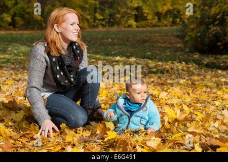 Indian Summer: junge Frau mit ihrem Baby im Herbst. Familienkonzept für Alleinerziehende. - Stockfoto