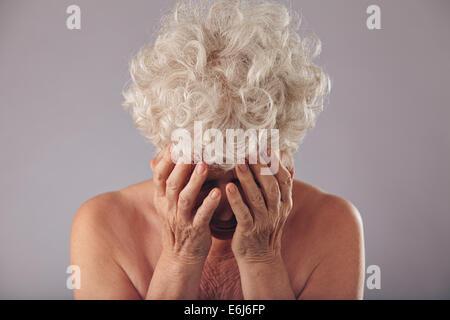 Porträt von unglücklich alte Dame He Gesicht in den Händen nach unten vor grauem Hintergrund halten. Traurige senior - Stockfoto