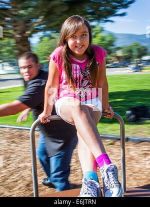 Vater seiner sieben Jahre alten Tochter auf einem Spielplatz-Karussell dreht - Stockfoto