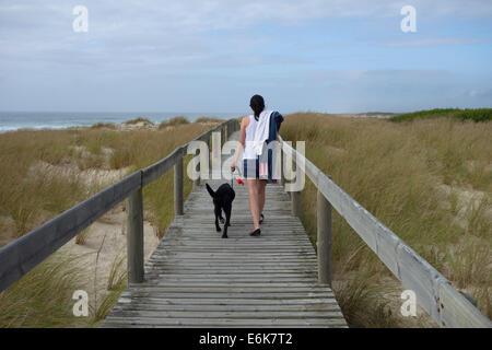 Rückansicht einer jungen Frau zu Fuß einen schwarzen Labrador Retriever Hund an der Leine auf einem Holzsteg über - Stockfoto
