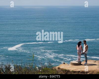 Junges Paar auf einer Klippe am Meer - Stockfoto