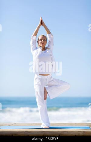 passen Sie Reife Frau Yoga Übung im Freien am Strand - Stockfoto