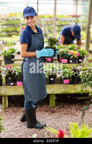 Porträt der jungen Floristin hält einen Topf mit Blumen im Gewächshaus