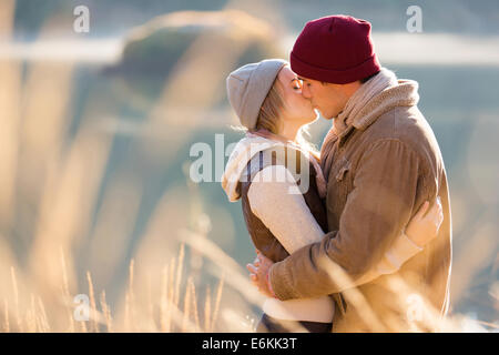 junges Liebespaar am See im Wintermorgen küssen