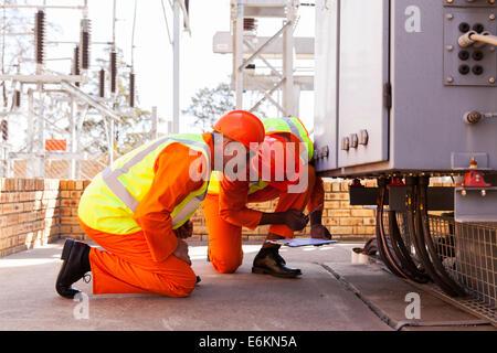 erfahrene Elektroingenieure arbeiten im Umspannwerk - Stockfoto