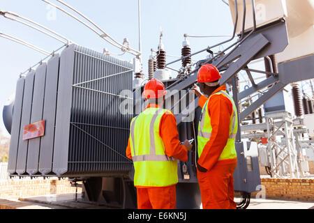 Rückansicht der Elektriker stehen neben einem Transformator im Elektrizitätswerk - Stockfoto