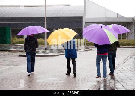 vier Personen unter bunten Regenschirm - Stockfoto