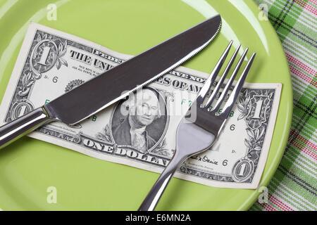 Ein-Dollar-Diät. 1 Dollar auf einem Teller mit Messer und Gabel. - Stockfoto
