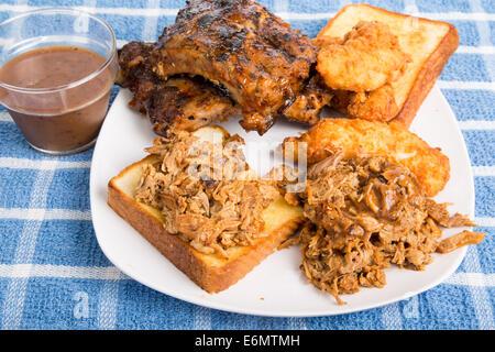 Grill-Teller mit gehacktem Schweinefleisch Sandwich, Rack von Rippen und Huhn Finger - Stockfoto
