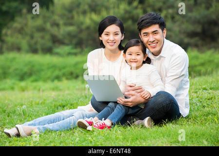Glückliche Familie mit Laptop auf dem Rasen - Stockfoto