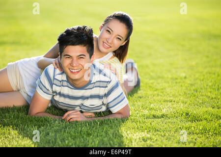 Fröhliches junges Paar auf dem Rasen liegend - Stockfoto