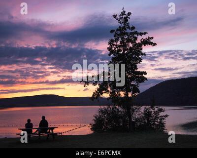 Lac de Chalain Sonnenuntergang, Jura, Frankreich mit zwei Silhouette Leute sitzen auf einem Picknick-Tisch, Blick - Stockfoto