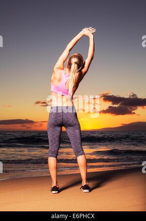 Sportliche Fitness Frau Strecken am Strand bei Sonnenuntergang - Stockfoto