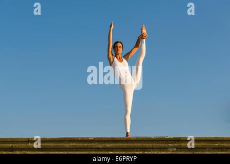 Junge Frau praktizieren Hatha Yoga im Freien, hob zeigen die Pose Anjaneyasana, die Hand um die Pose zu Fuß - Stockfoto