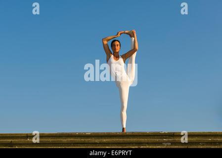 Junge Frau praktizieren Hatha Yoga im Freien, hob zeigen die Pose Utthita Hasta Pandangusthasana, die Hand zur Großzehe - Stockfoto