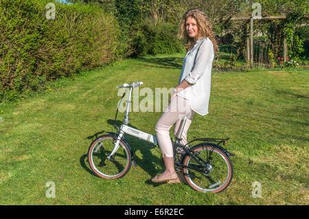Eine hübsche junge Frau sitzt auf ihrem Dahon Faltrad in einem Garten in Surrey, England, UK. - Stockfoto