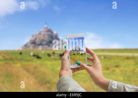 Mädchen fotografieren auf einem Handy, Le Mont Saint Michel Abbey, Normandie / Bretagne, Frankreich - Stockfoto