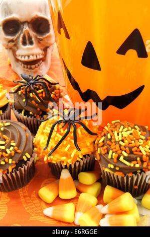 Halloween-Stillleben mit Muffins, Süßigkeiten und Dekor - Stockfoto