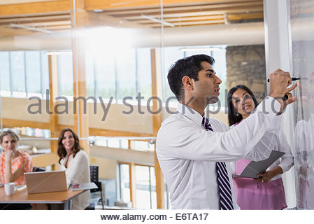 Geschäftsmann auf Tafel in Besprechung schreiben - Stockfoto