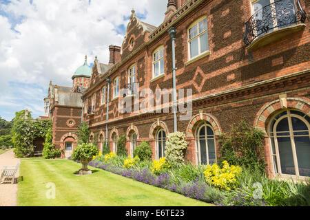 Hintere Fassade von Sandringham House, Norfolk Country House Rückzug der Königin, mit feinen roten Ziegel Mauerwerk und Blumenrabatten, im Sommer