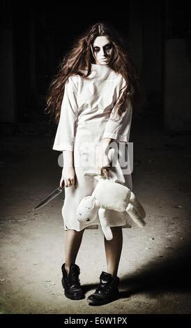 Horror-Szene: ein gruseliges Monster Mädchen mit Puppe Mizzi und Messer in Händen - Stockfoto