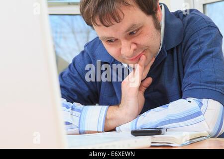 Ingenieur und Programmierer mit Asperger auf seinem Computer von zu Hause aus arbeiten - Stockfoto